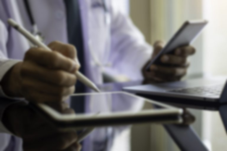 Blurred image of male doctor looking at phone and writing on tablet