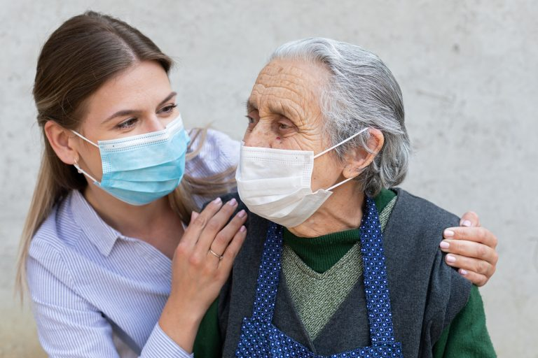 Caregiver with elderly person, both wearing masks