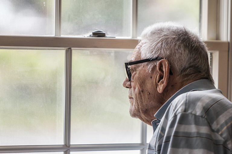 Wistful Senior Man Staring Through Hazy Window