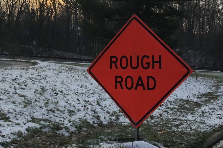 Rough road sign next to snow-covered median