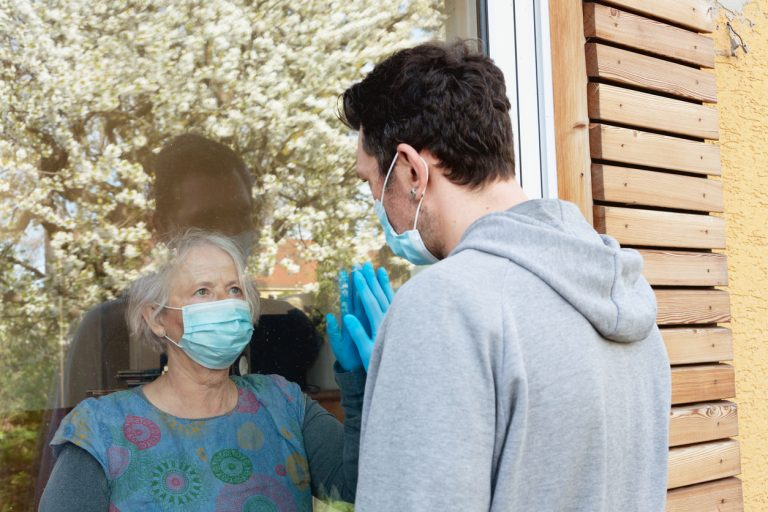Senior woman wearing mask visiting middle age man wearing mask through window