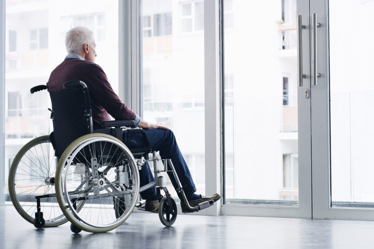 person in wheelchair looking out window