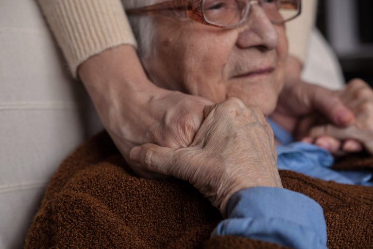 senior woman holding hands with someone